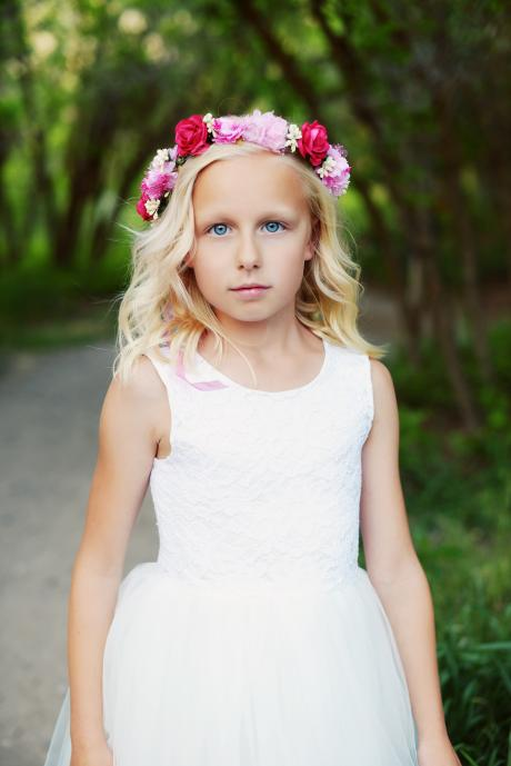 A beautiful red and pink floral head crown worn by a flower girl in an ivory lace flower girl dress.
