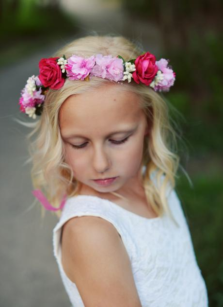 A flower girl head band in pink and red worn by a little flower girl at a wedding.