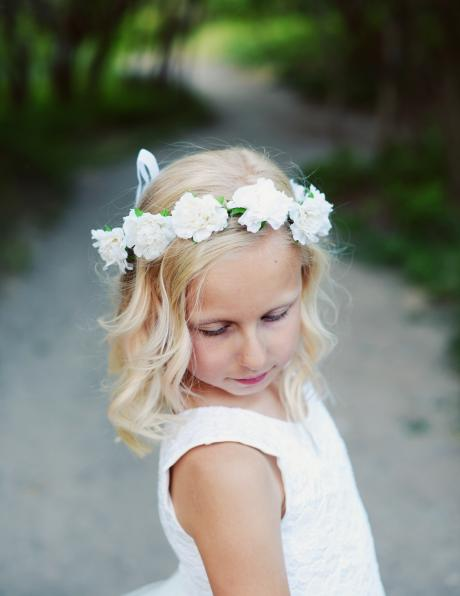A flower girl on a path in the woods wearing a white lace first communion dress with a with flower head crown.