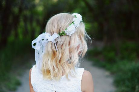 A girl on a path in the woods wearing a white lace flower girl dress and showing the back of a white flower girl crown with white flowers..