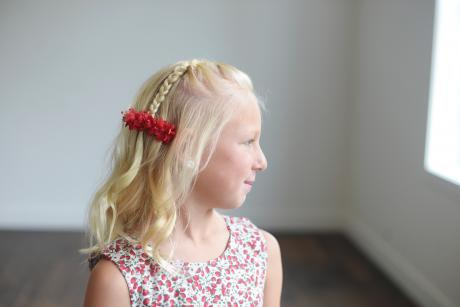 A flower girl and a junior bridesmaid wearing a red flower girl hair clip with anemones.
