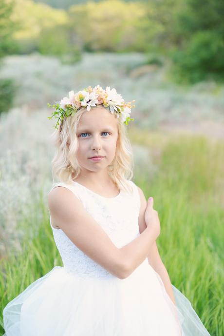 A flower girl and junior bridesmaid in a field with flowers wearing an ivory flower girl dress and a white junior bridesmaid dress, Both girls wear yellow floral hair crowns.