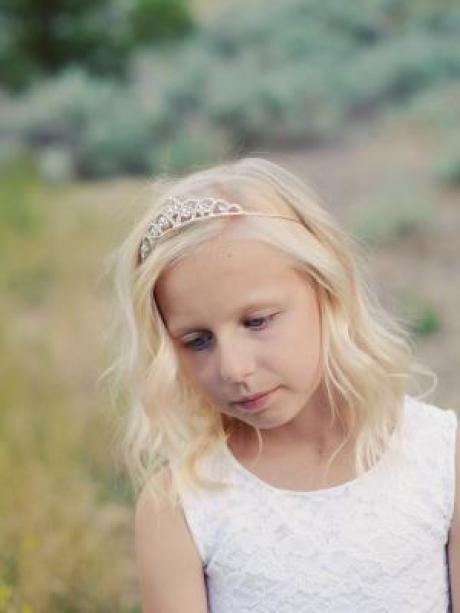 A girl wearing a white lace dress and a diamanté tiara