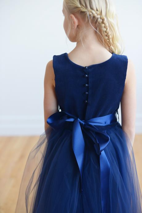 The back of a navy blue velvet flower girl dress with a big satin ribbon bow and a full button up back.