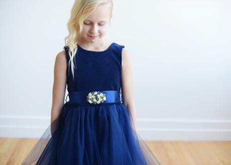A young flower girl at a wedding wearring a beautifully soft  woven navy  blue velvet flower girl dress with a tulle skirt and diamante motif