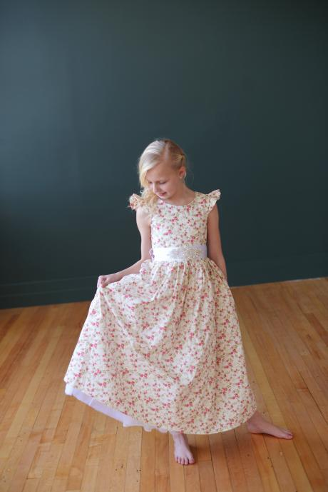 Two young girls wearing a flower girl dress and a junior bridesmaid dress in a floral print with butterfly sleeves.