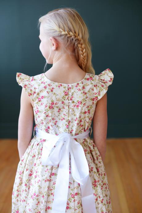 A very pretty floral flower girl dress available in pink, blue, green, yellow, navy and purple with butterfly sleeves and a pouffy skirt.