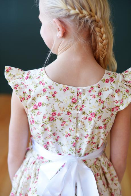 The full button back of a floral flower girl dress with butterfly sleeves, a round neck and is floor length.