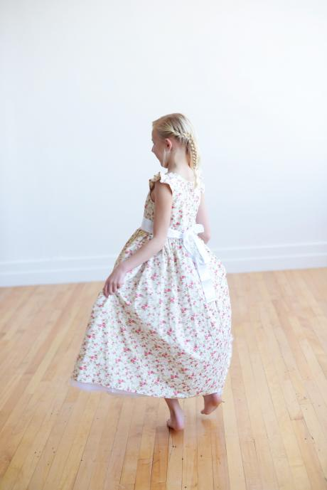 A young girl showing the side of a floral flower girl dress with sleeves and a sash which ties in a big bow.