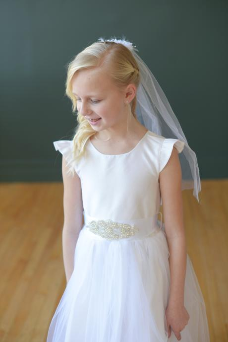 A girl taking her first communion wearing a white or ivory first communion dress and a veil with delicate flowers on a barrette hair clip. Made in London, UK.