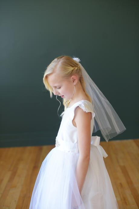 A girl taking her first communion and wearing aa white flower girl dress with a tulle skirt and silk bodice and wearing a delicate veil with white tulle and anemone flowers.