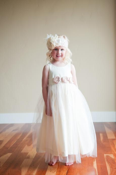 A full length photo of a young flower girl wearing a designer cotton flower girl dress or junior bridesmaid dress with a tulle skirt and blush pink roses on the sash.