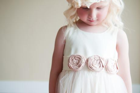 A close up of a young flower girl wearing a designer cotton flower girl dress in Victorian style with blush pink flower roses.