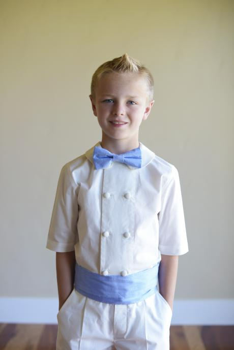 A pageboy wearing a  baby blue bow tie, an ivory shorts and shirt set and a blue cummerbund.