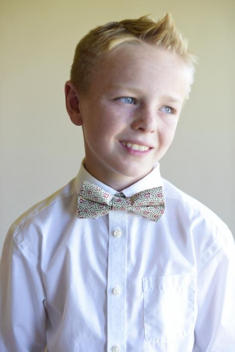 A page boy wearing a pre tied boys bow tie in a dark red, green and ivory floral pattern with  yellow accents.