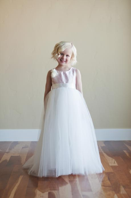 A young flower girl at a wedding wearing a pink and white flower girl dress with a silk bodice and a tulle skirt.