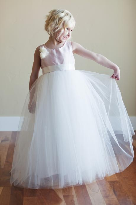 A young flower girl wearing a flower girl dress in ivory and blush pink. The dress has a tulle skirt and an organza flower.