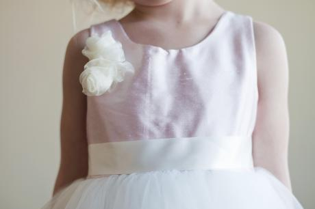 A close up of a girl wearing a blush pink flower girl dress with flower on shoulder and a tulle skirt for toddlers and junior bridesmaids