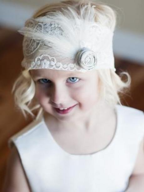 A young girl wearing an elasticated flower girl headband with a grey silk flower and feather detail.