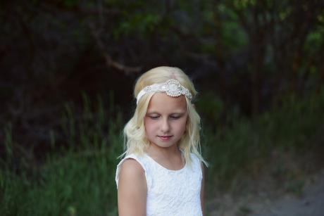 A junior bridesmaid and a flower girl wearing an ivory lace junior bridesmaid dress with the flower girl wearing an ivory flower girl dress. Both the junior bridesmaid and the flower girl have elasticated diamante headbands.