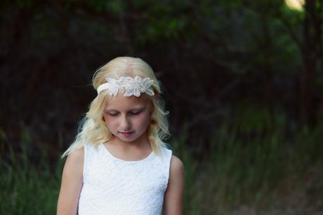 A junior bridesmaid wearing a white flower girl dress with lace bodice and tulle skirt. The junior bridesmaid is also wearing an elasticated flower girl headband with diamante trim.