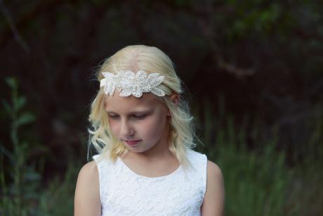A flower girl at a rustic wedding wearing an ivory lace flower girl dress with a tulle skirt and a junior bridesmaid wearing a white junior bridesmaid dress. The girls are both wearing an elasticated flower girl headband with a diamante trim