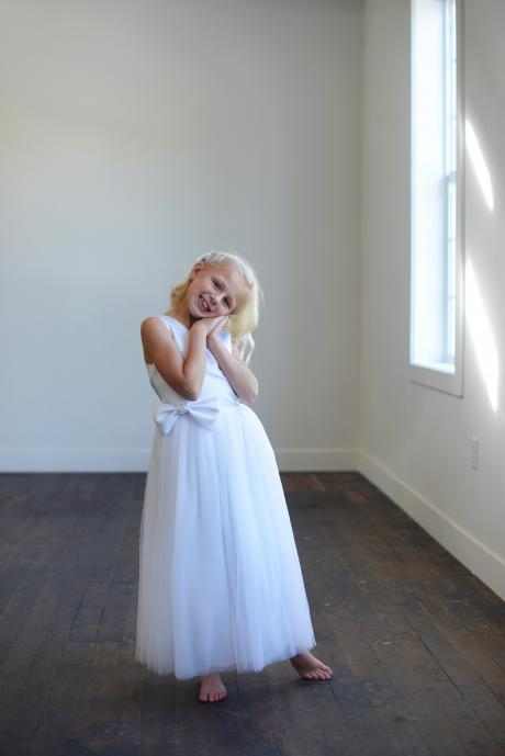 A girl standing by a window wearing a made to measure pretty first communion dress in white satin with a tulle skirt