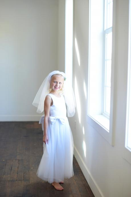 A girl wearing a handmade white satin first communion dress with a veil with diamanté embellishment
