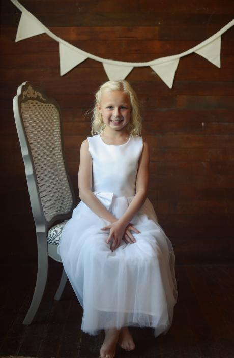 A handmade flower girl wearing a made to measure dress in satin with a tulle skirt and pretty bow