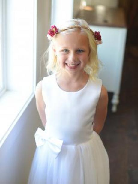 A flower girl wearing a hand made red floral crown