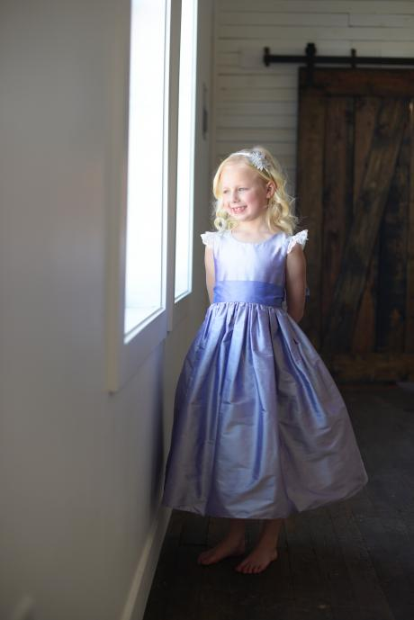 A young flower girl at a wedding looking out of a window. The dress is made in cornflower blue silk with lace sleeves and has a big bow