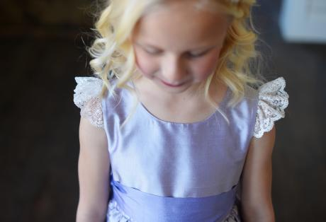 A close up of a flower girl at a wedding wearing a blue, silk flower girl dress with lace sleeves and a round high neckline.