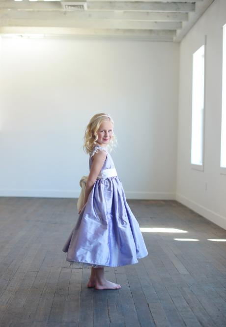 A girl standing in a room at a wedding showing the side view of her cornflower blue silk flower girl dress with lace sleeves.