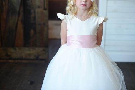 A girl wearing a first communion dress with a sweetheart neck, wide silk pink bow and a full tulle skirt. The bodice is made in silk.