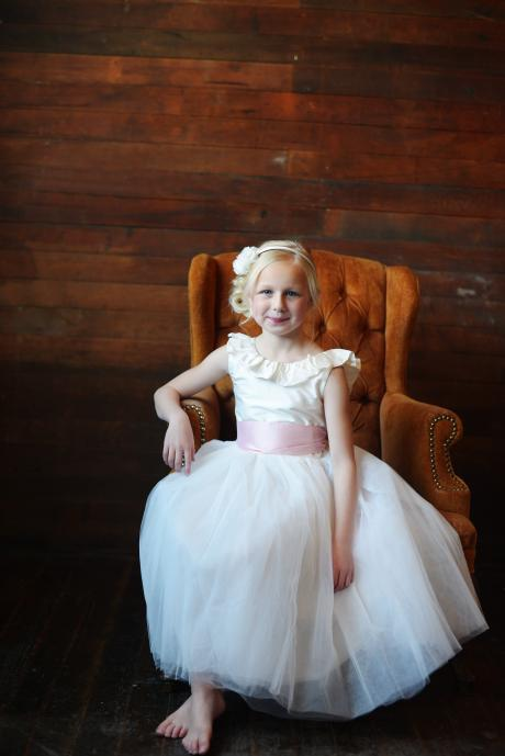 A young flower girl sitting on a chair wearing a silk flower girl dress with a ruffled v neckline and a wide sash.