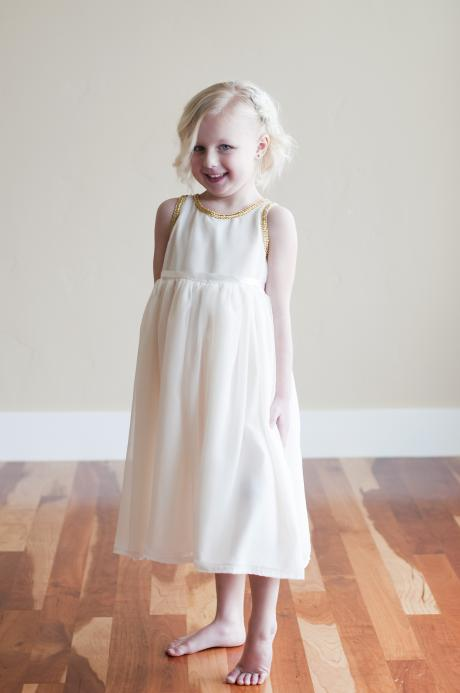 A baby flower girl and a toddler flower girl wearing an ivory chiffon flower girl dress with gold piping. The flower girl dress is gathered at the waist and gold trim goes around the neck line and bodice.