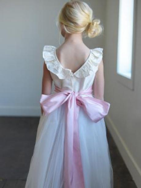 The back of a v neck dress with ruffle necking and tulle skirt. The dress has a wide pink sash with big bow.
