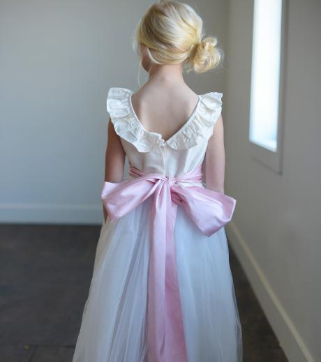 The back of a v neck flower girldress with ruffle necking and tulle skirt. The dress has a wide pink sash with big bow.