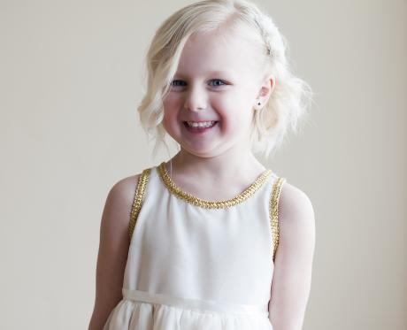 A close up of a toddler flower girl wearing a white chiffon flower girl dress with gold trim around the neckline. The dress has a very full chiffon skirt and a ribbon sash.