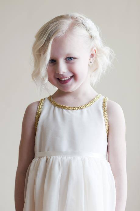 A toddler flower girl wearing a chiffon flower girl dress in ivory with gold trim around the neckline and a ribbon belt.
