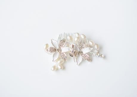 A beautiful silver bridal hair comb for brides and briesmaids or flower girls. The comb has white accents on the two large flowers and is surrounded with small diamante and pearls.