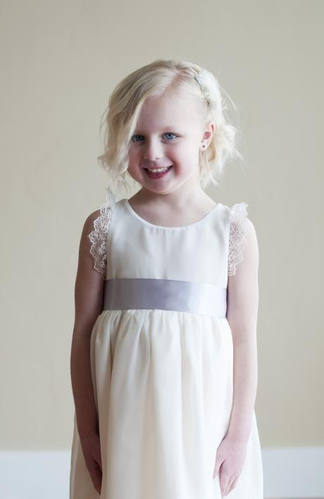 A toddler wearing a flower girl dress in ivory chiffon with silver braid around the neckline and a silver satin sash.