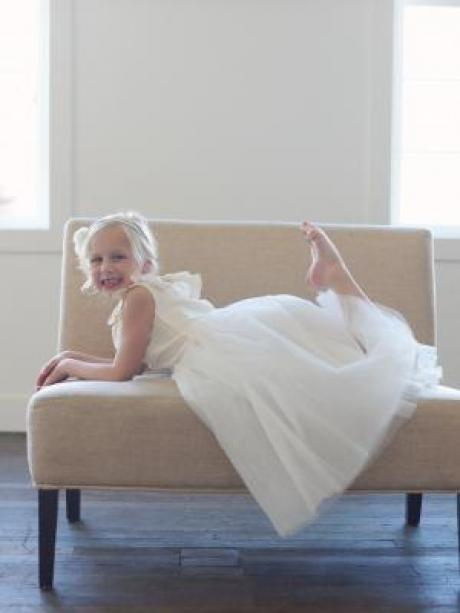 A girl on a couch wearing an ivory silk flower girl dress with v back and full tulle skirt.