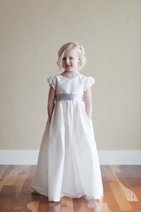 A floor length First Communion dress with a button back and puffed sleeves.