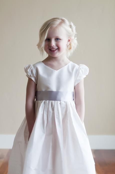 A young girl at her first communion wearing a classic white first communion dress with puff sleeves and v neck.