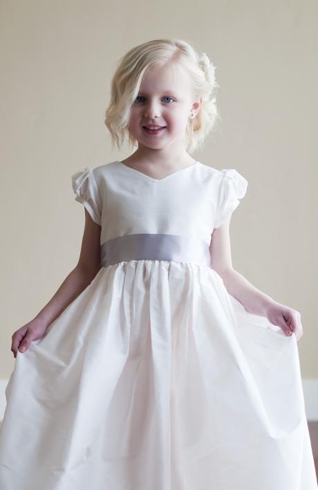 A girl taking her first communion in a church wearing a white silk first communion dress which has puff sleeves and a long sash bow.