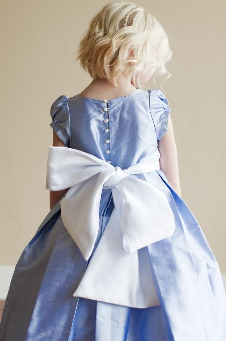 The back of a blue flower girl dress with a full button back and a big sash and bow.