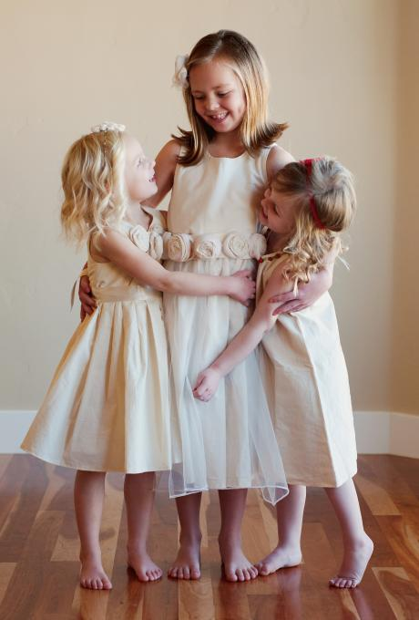 Three flower girls and a junior bridesmaid wearing ivory cotton flower girl dresses and an ivory cotton junior bridesmaid dress with flowers at the wasit.