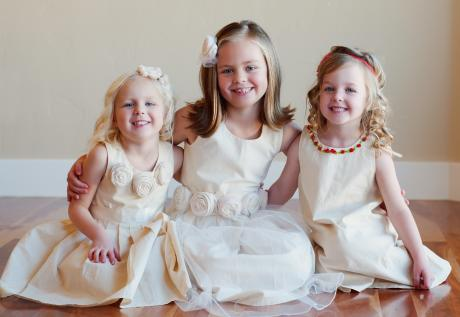 A group of flower girls and junior bridesmaids wearing cotton flower girl dresses in ivory and junior bridesmaid dresses in white with roses around the collar.