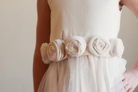 A junior bridesmaid dress and a flower girl dress in a soft ivory cotton with a tulle skirt and roses on the sash.